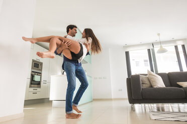 Playful young man carrying girlfriend at home - SIPF01595