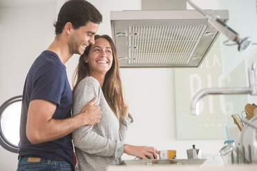 Happy young couple in love with coffee cups in kitchen - SIPF01601