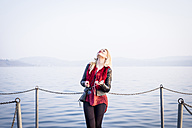 Blond woman standing in front of a lake listening music with smartphone and earphones looking up - SIPF01603