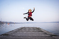 Blond woman jumping in the air on a jetty - SIPF01606