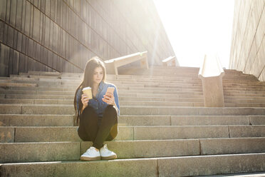Young woman with coffee to go sitting on stairs looking at cell phone - VABF01296