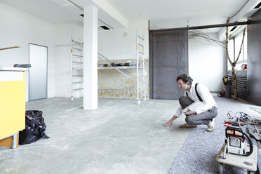 Architect checking screed at construction site - REAF00243