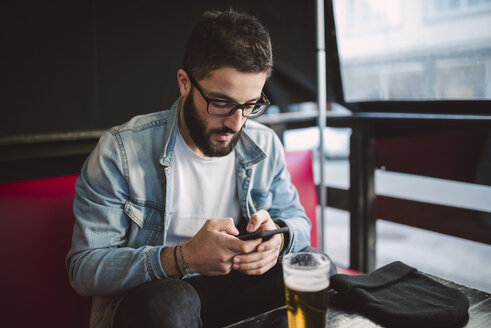Young man text messaging in a pub - RAEF01808