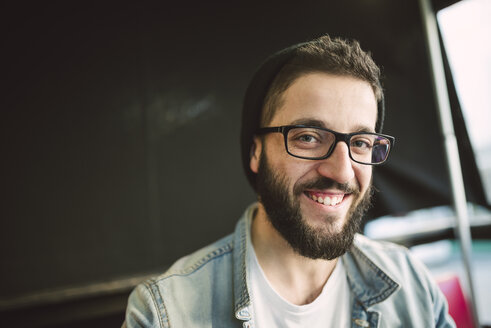 Portrait of bearded young man wearing glasses and hat - RAEF01814