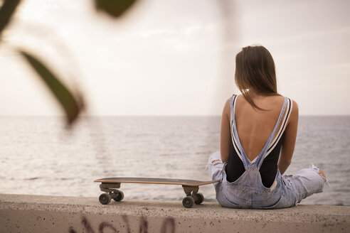 Back view of woman with skateboard sitting on a wall in front of the sea - SIPF01608