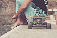 Woman with skateboard sitting on a wall, partial view - SIPF01611