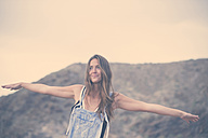 Portrait of smiling woman with arms outstretched - SIPF01614