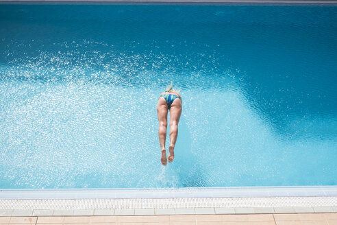 Woman jumping into swimming pool - SIPF01620