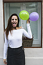 Portrait of young woman writh ballons sticking out tongue - KKAF00650
