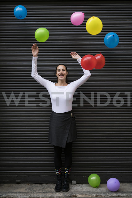 Happy young woman standing in front of black roller shutter with flying balloons - KKAF00653