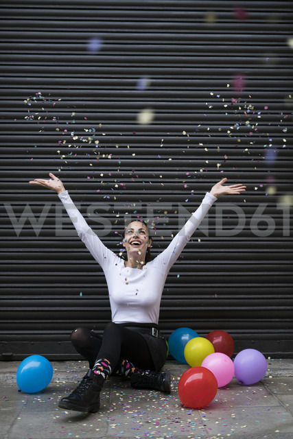 Happy young woman sitting on pavement with balloon throwing confetti - KKAF00656