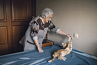 Senior woman playing with her cat at home - RAEF01820