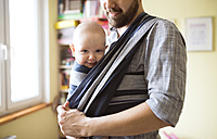Father with baby son in sling at home - HAPF01407