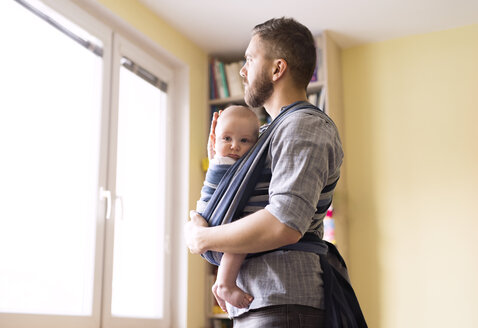 Father with baby son in sling at home looking out of window - HAPF01413