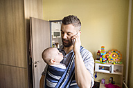 Father with baby son in sling at home talking on cell phone - HAPF01419