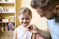 Father at home caring for daughter having chickenpox - HAPF01422