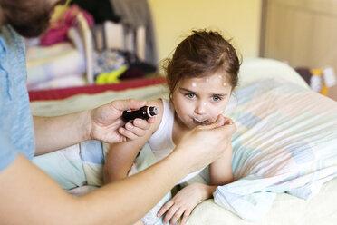 Girl having chickenpox receiving medicine in bed - HAPF01428