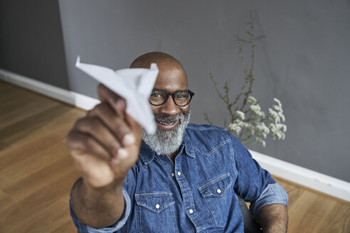 Mature man plying with paper plane - FMKF03740