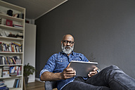 Mature man using digital tablet - FMKF03743