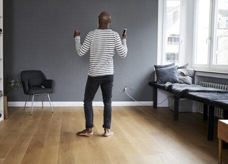Mature man dancing alone at home, holding smart phone - FMKF03752