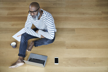 Mature man sitting on floor, working on laptop - FMKF03758