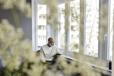 Mature man sitting at window, reading a book - FMKF03761