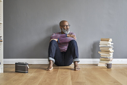 Mature man sitting on floor listening to the radio, looking serious - FMKF03767