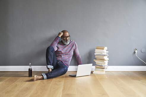 Mature man sitting on floor, using laptop - FMKF03770