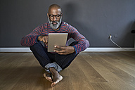 Mature man using digital tablet - FMKF03773