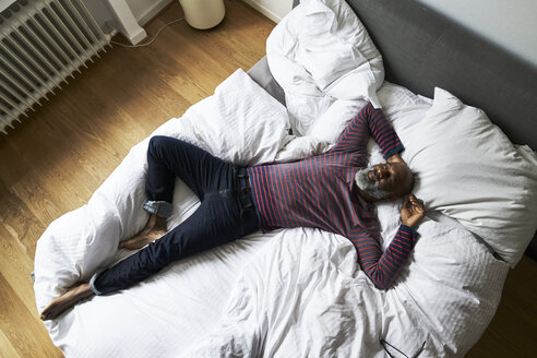 Mature man lying on bed, smiling - FMKF03776