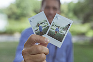 Man's hands holding instant photos - BOYF00754