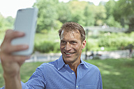 Portrait of smiling man taking selfie with smartphone in a park - BOYF00757