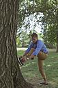 Man tying shoes in a park - BOYF00760