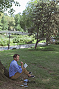 Man sitting on a meadow in a park  with notebook - BOYF00763