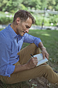 Man with notebook sitting on a meadow in a park writing down something - BOYF00766