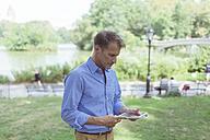 Man using mini tablet in a park - BOYF00769