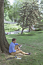 Man with tablet sitting on a meadow in a park - BOYF00772
