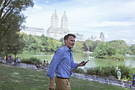 USA, Manhattan, Central Park, smiling man with cell phone and earphones - BOYF00775