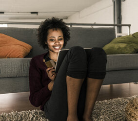 Smiling young woman at home holding credit card and tablet - UUF10317