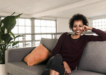 Portrait of smiling young woman sitting on couch - UUF10320