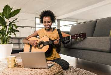 Smiling young woman at home playing guitar looking at laptop - UUF10323