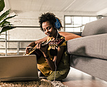 Young woman at home with headphones and laptop playing guitar - UUF10326
