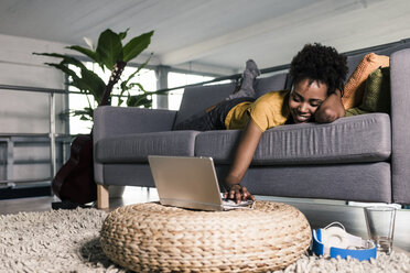 Smiling young woman lying on couch using laptop - UUF10332