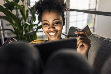 Smiling young woman on couch with credit card and laptop - UUF10335