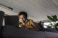 Smiling young woman with headphones lying on couch using laptop - UUF10338