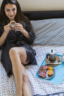 Portrait of smiling young woman sitting on bed in the morning having breakfast - KKAF00667