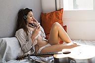 Smiling young woman sitting on bed with cell phone listening music with headphones - KKAF00673