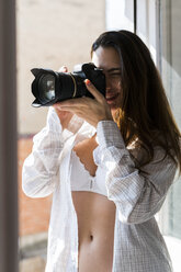 Smiling young woman taking picture with camera in front of open window - KKAF00682