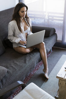 Young woman sitting on the couch at home in the morning using laptop - KKAF00685