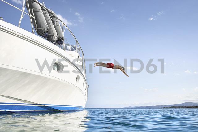 Man jumping off his motor yacht - PDF01084 - Philipp Dimitri/Westend61